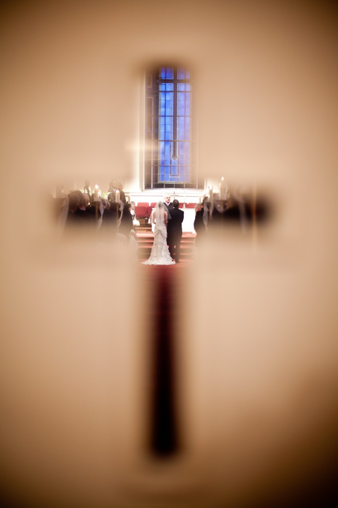View of wedding through the crucifix shaped window in the sanctuary doors